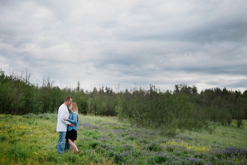 Edmonton engaged couple embraces under moody sky