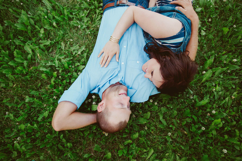 engaged couple wears blue cuddles on grass in Edmonton