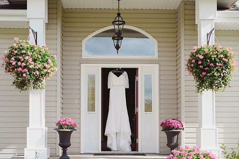 Stunning wedding dress with sleeves hangs in the bride's doorway prior to her University of Alberta wedding with a . Faculty Club reception in Edmonton